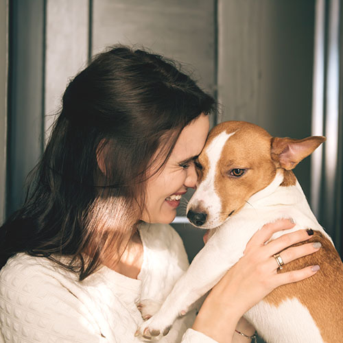 beautiful smiling woman hugging her dog at home